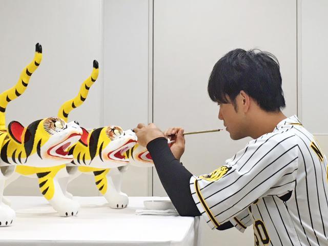 張り子の虎に目入れする阪神タイガース選手会副会長の中谷将大選手