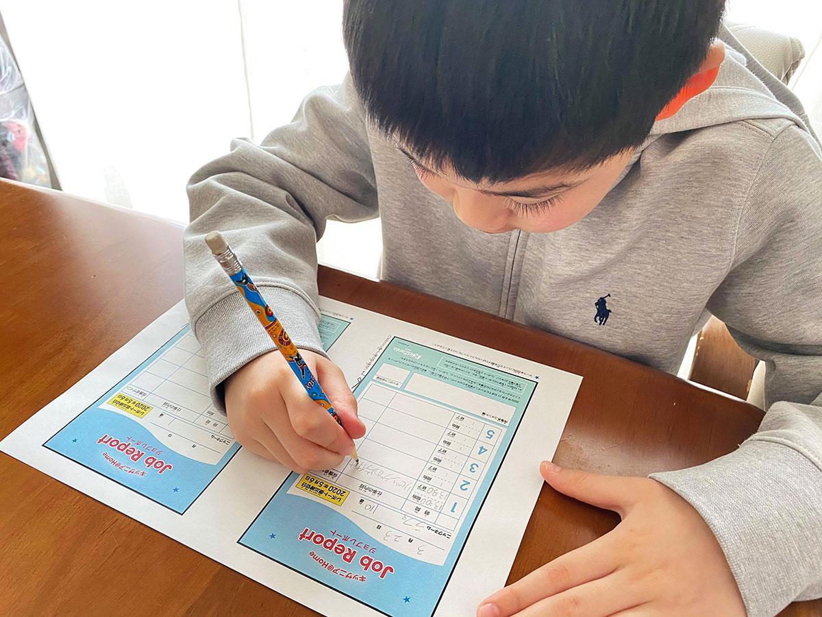 ジョブレポート用紙に仕事内容を記入する小学生