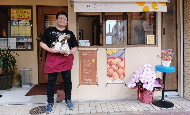 店頭で「芦屋べびか」を手にする店主の植野匡英さん
