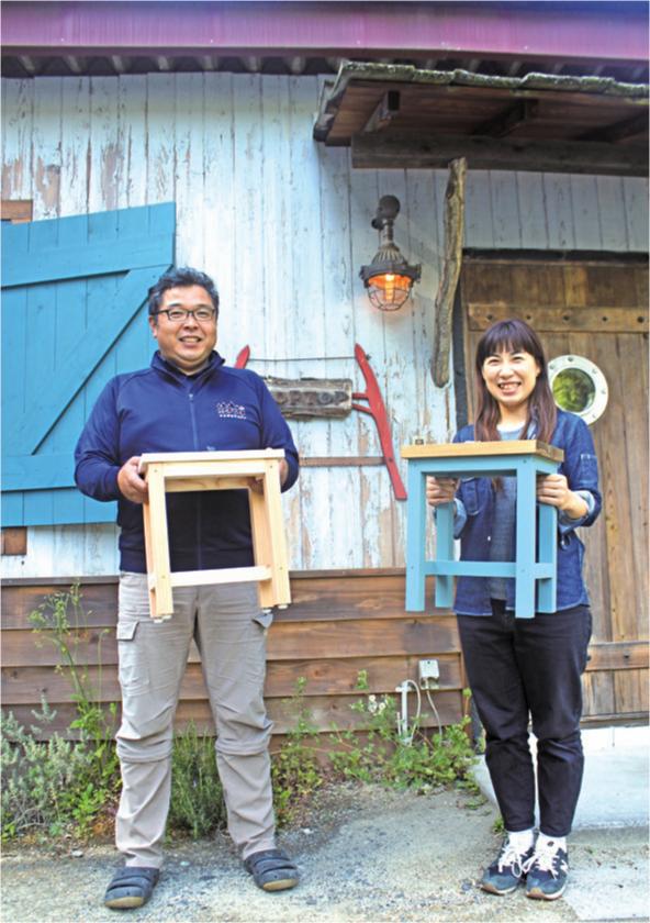 キットで作ったスツールを持つ代表取締役の清水有二さんと藤野さん