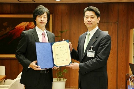 加藤市長(右)より「任命書」を受け取る合田雅吏さん(左)(写真=4月2日、市長室で行われた就任式の様子)