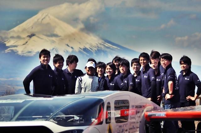 工学院大学の濱根洋人監督(准教授)とチームのメンバー。手前はソーラーカー「OWL(あうる)」と奥に富士山