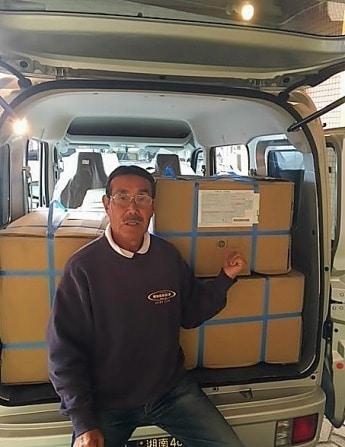 「GODDESS(ゴッデス)」を経営するゴッデスインターナショナル(茅ケ崎市中海岸)の鈴木正社長。段ボールはカンボジアに送るビーチサンダル