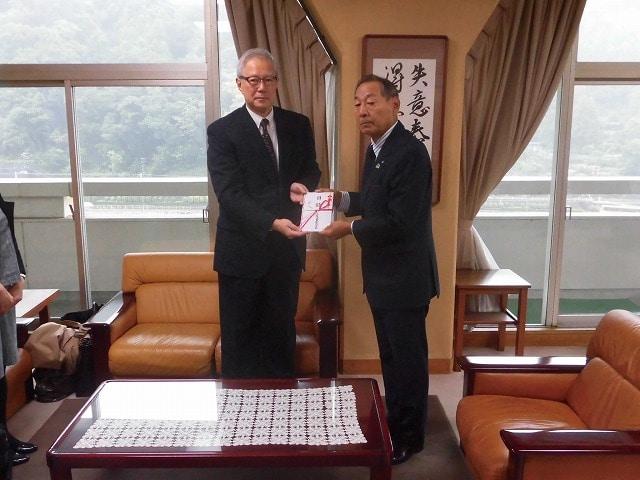 金子一郎常務(左)から山口昇士箱根町長(右)へ寄付目録が渡された(10月16日、箱根町の町長室で)