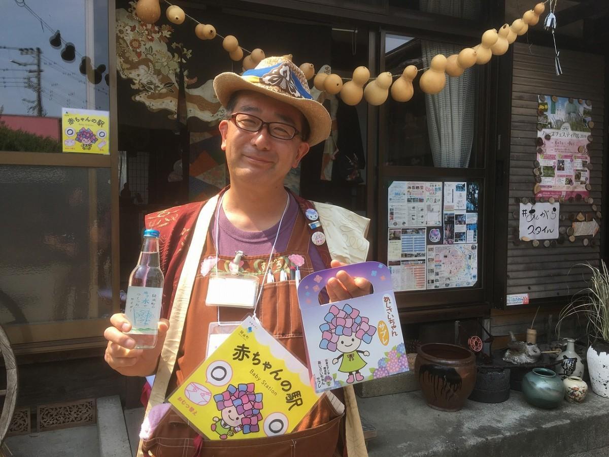 「古民家ガーデン紋蔵」の入り口でゲストを迎える志澤晴彦さん。「あじさいちゃんサブレ」には、開成町の地下水で作られたサイダーも良く合うとアピール