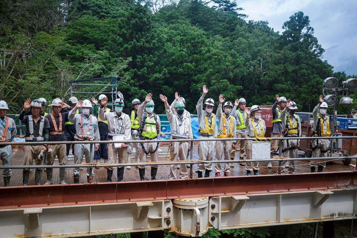 蛇骨陸橋の工事現場で関係者が手を振って乗客を迎える(撮影=大橋史明)