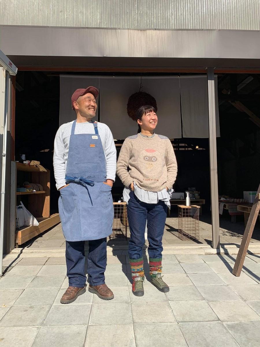 たき火用エプロン。杉山大輔さん(左)とデザイン・製作を担当した古谷友子さん(右)