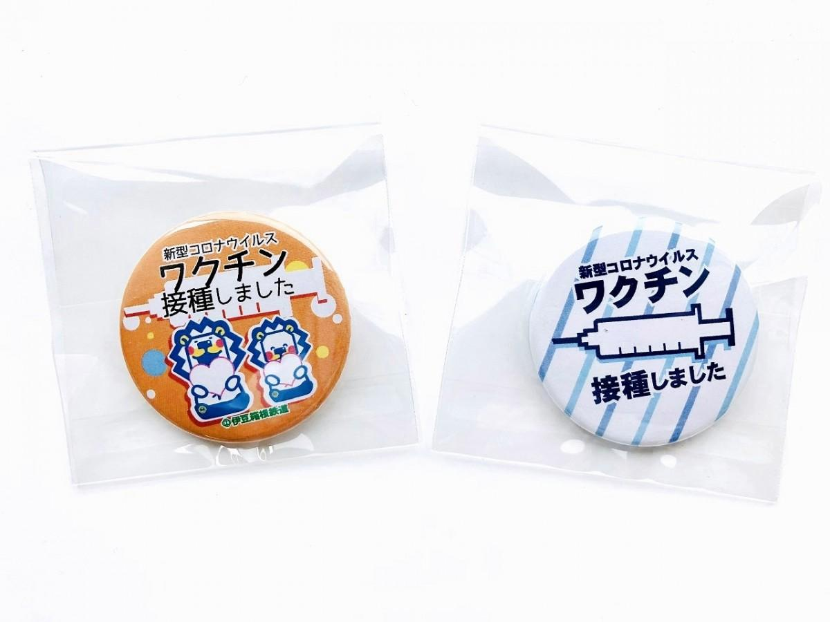 「ワクチン接種しました」缶バッジ。「ライオンになりたいネコバージョン」(左)と「注射器イラストバージョン」(右)