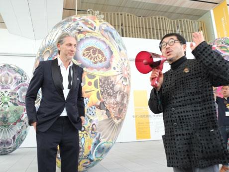 記者発表時に作品について説明する新見館長(右)とデザイナー、マルセル・ワンダースさん(左)
