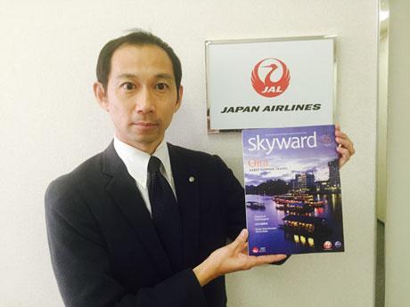 機内誌「SKYWARD」を手にする原山アシスタントマネジャー