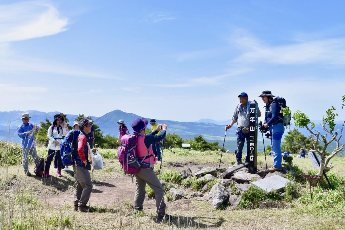 山頂で記念撮影する登山客