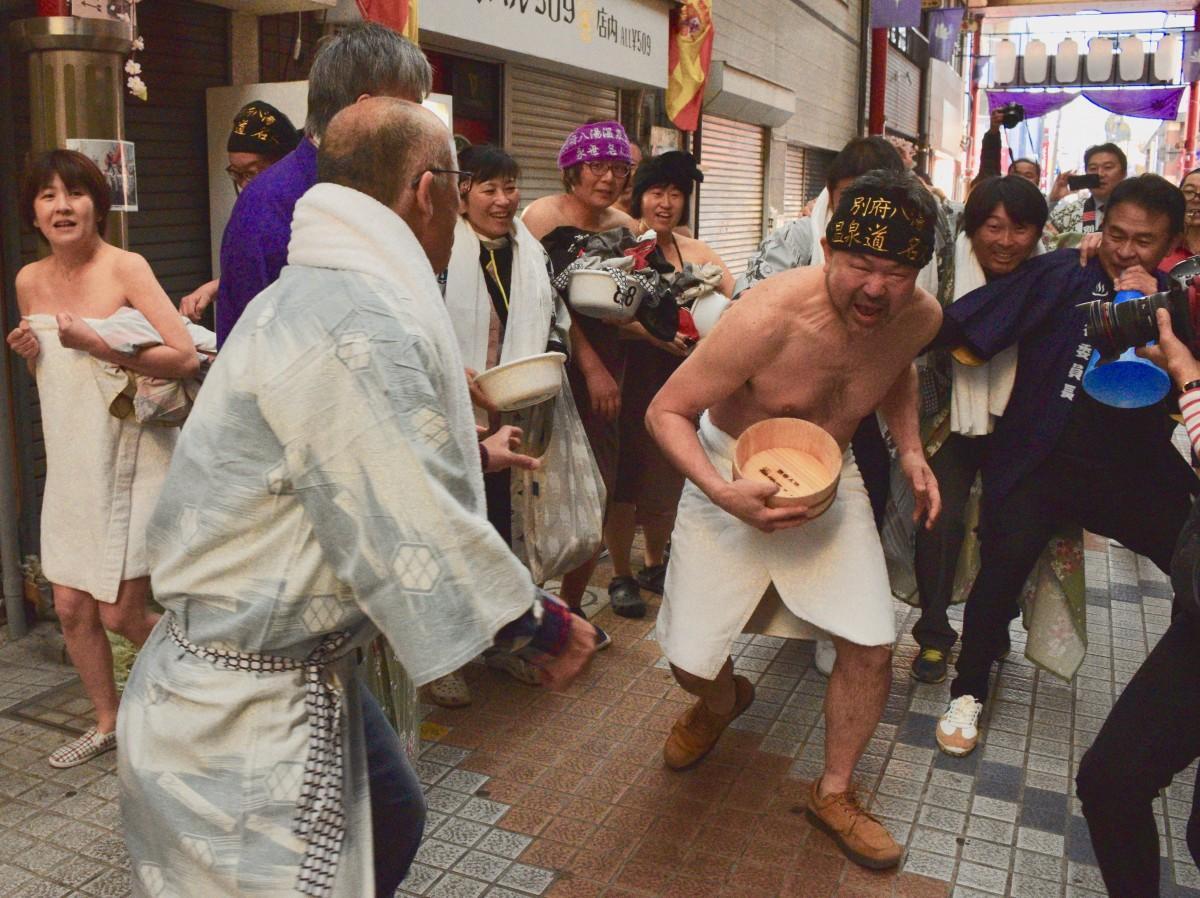 風呂おけを抱えて商店街を走る参加者
