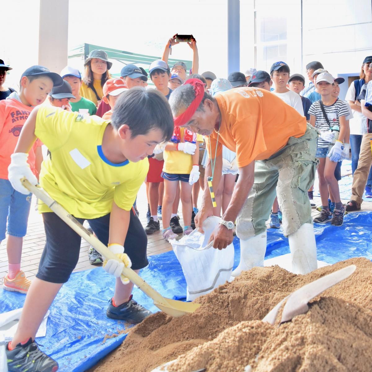 土のう作りに挑戦する小学生