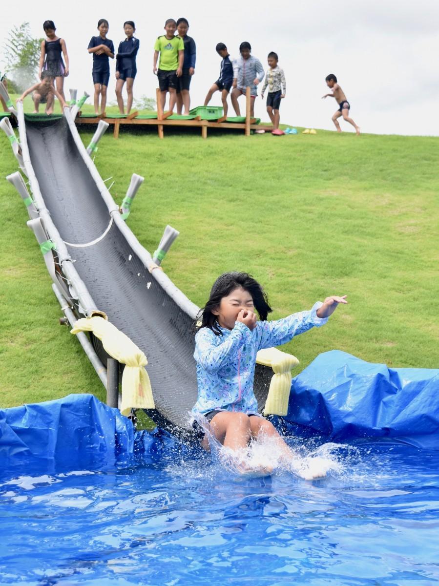 滑ってドボンッ!水滑りを楽しむ子どもたち