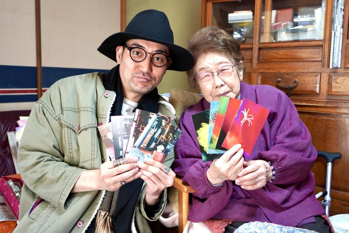 写真展を開くサヨさんと東京神父さん