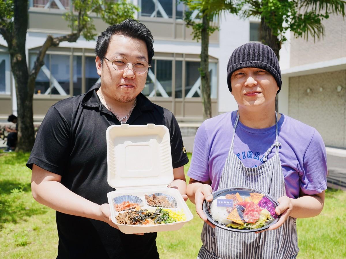 別府大で弁当を販売した梁原さんと(左)と釘宮さん