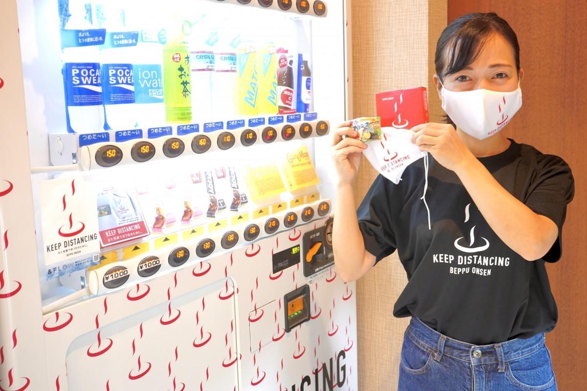 マスクを手に「ソーシャル・ディスタンシング」を呼び掛ける大塚さん