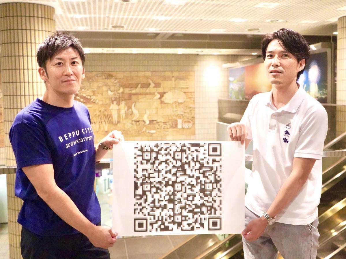 応募QRコードを手に呼び掛ける田邉さん(左)と小山秀輝さん