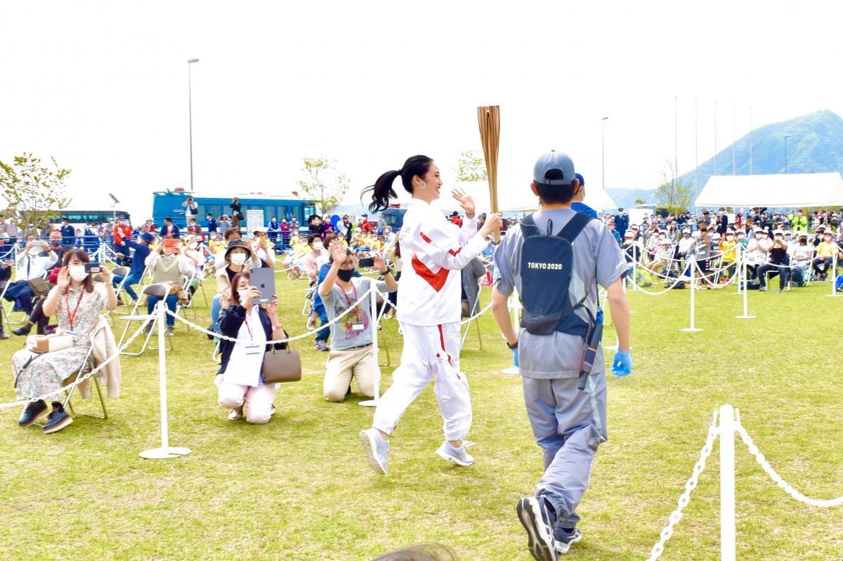 手を振りながら走る田中さん(別府国際観光港多目的広場で、4月23日10時4分撮影)