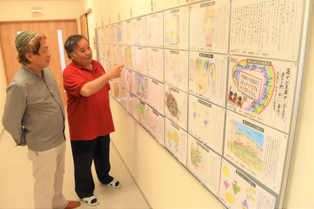 笑顔で作品を見る今村会長(右)と田代さん