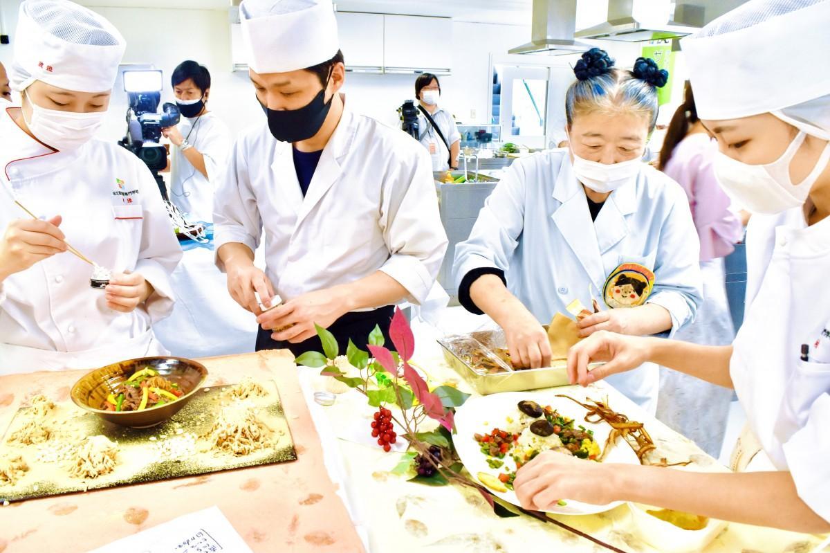 各月の「おおいた和牛」料理を盛り付ける生徒ら