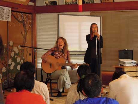 本堂で歌うアンニャ・ライトさんと娘のパチャさん