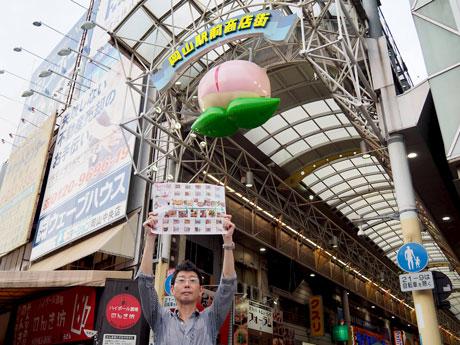 岡山駅前商店街入り口に設置された桃オブジェとマップをPRする土居和正さん