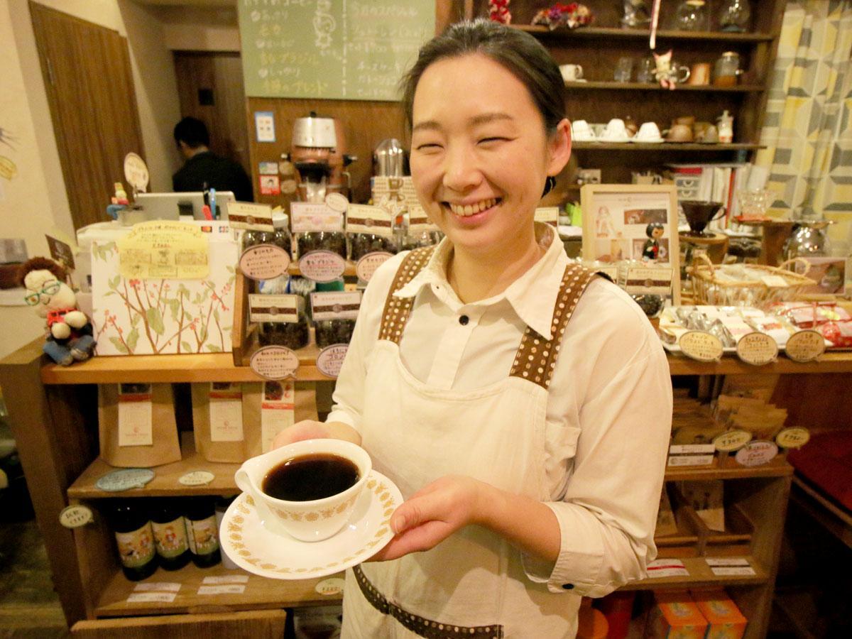 入れたての「香るブラジル」コーヒーを持つ店長の脇山夏海さん