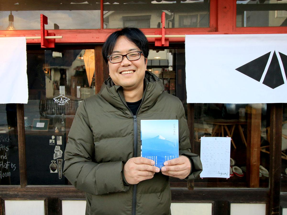 krAckの前で本を持つ小野博さん