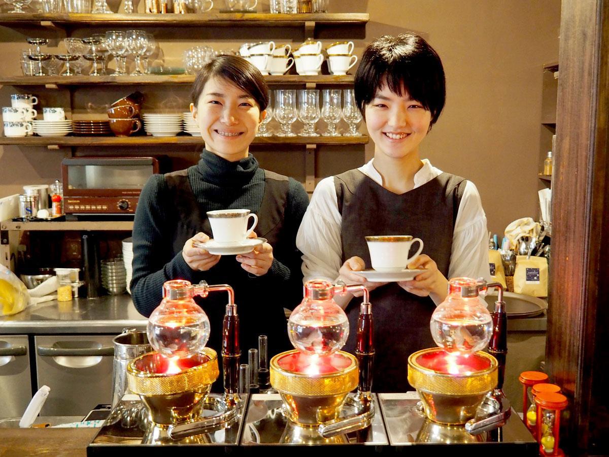 コーヒーサイホンを置いたカウンター奥に立つ真鍋紘美さん(左)と石井寛子さん(右)