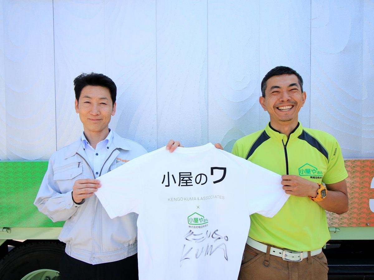 「小屋のワ」の前でサインTシャツを持つ植田博幸さん(左)と中山陽平さん(右)