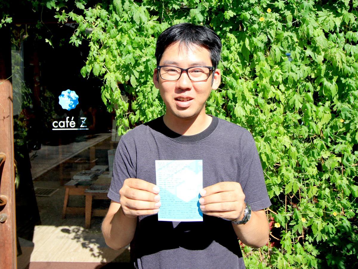 カフェZでポストカードを持つ白井崇裕さん