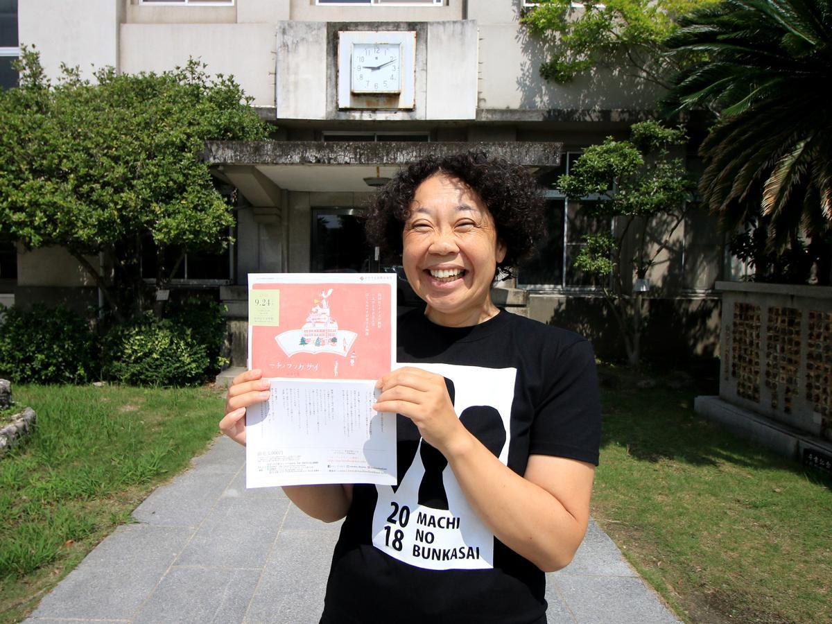 旧内山下小学校前でイベントチラシを持つ岡野英美さん