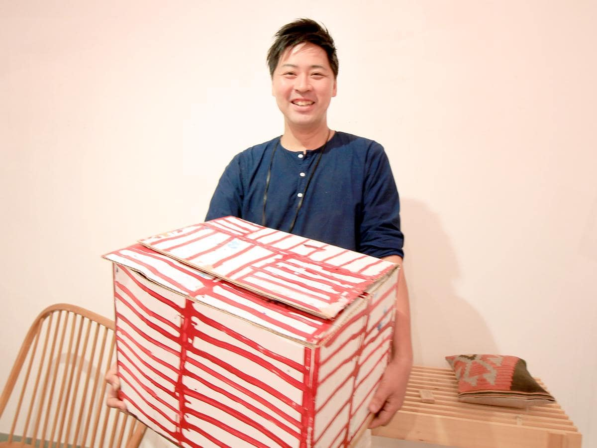 送られてきた箱を抱えるアクシス・クラシックの片岡弘之さん