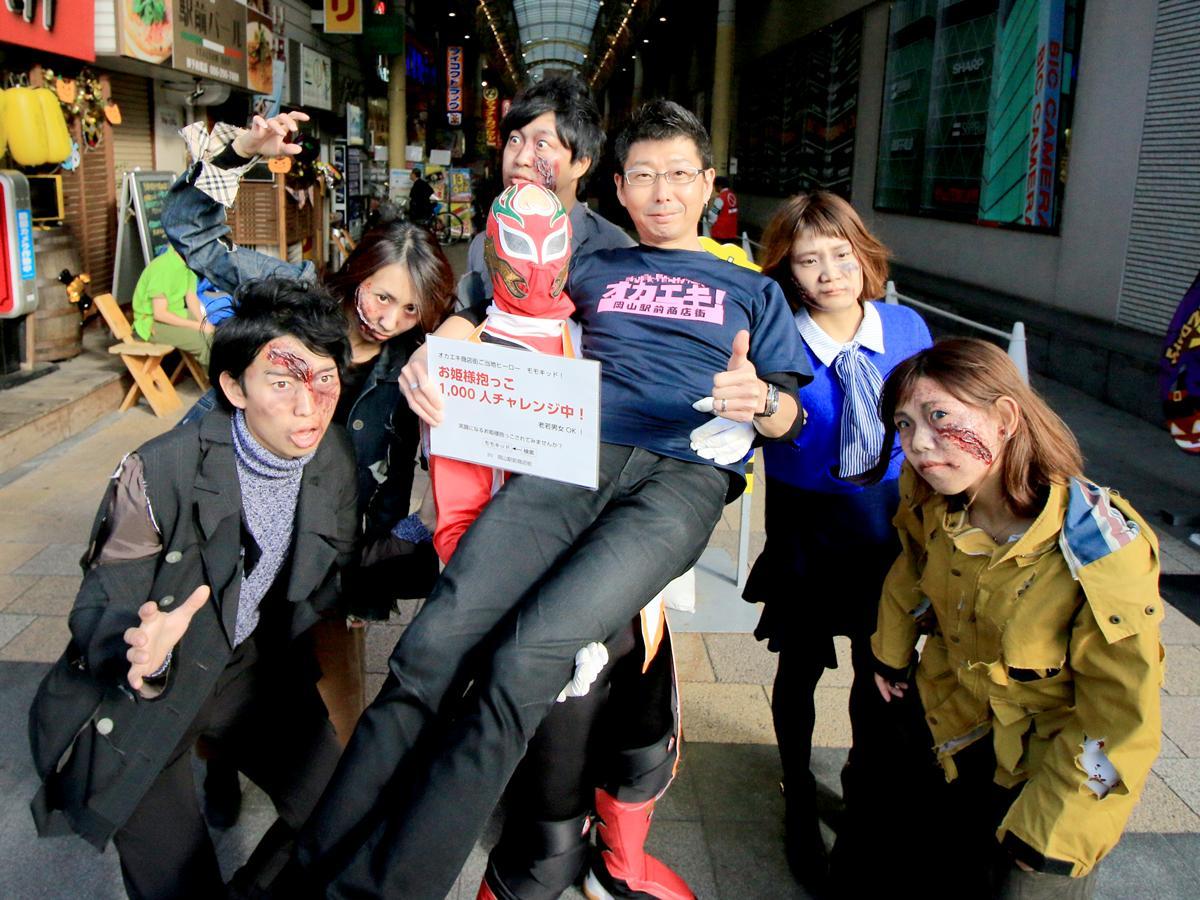ゾンビに扮装(ふんそう)した人たちと岡山駅前商店街青年部長・土居和正さんを抱っこするモモキッド