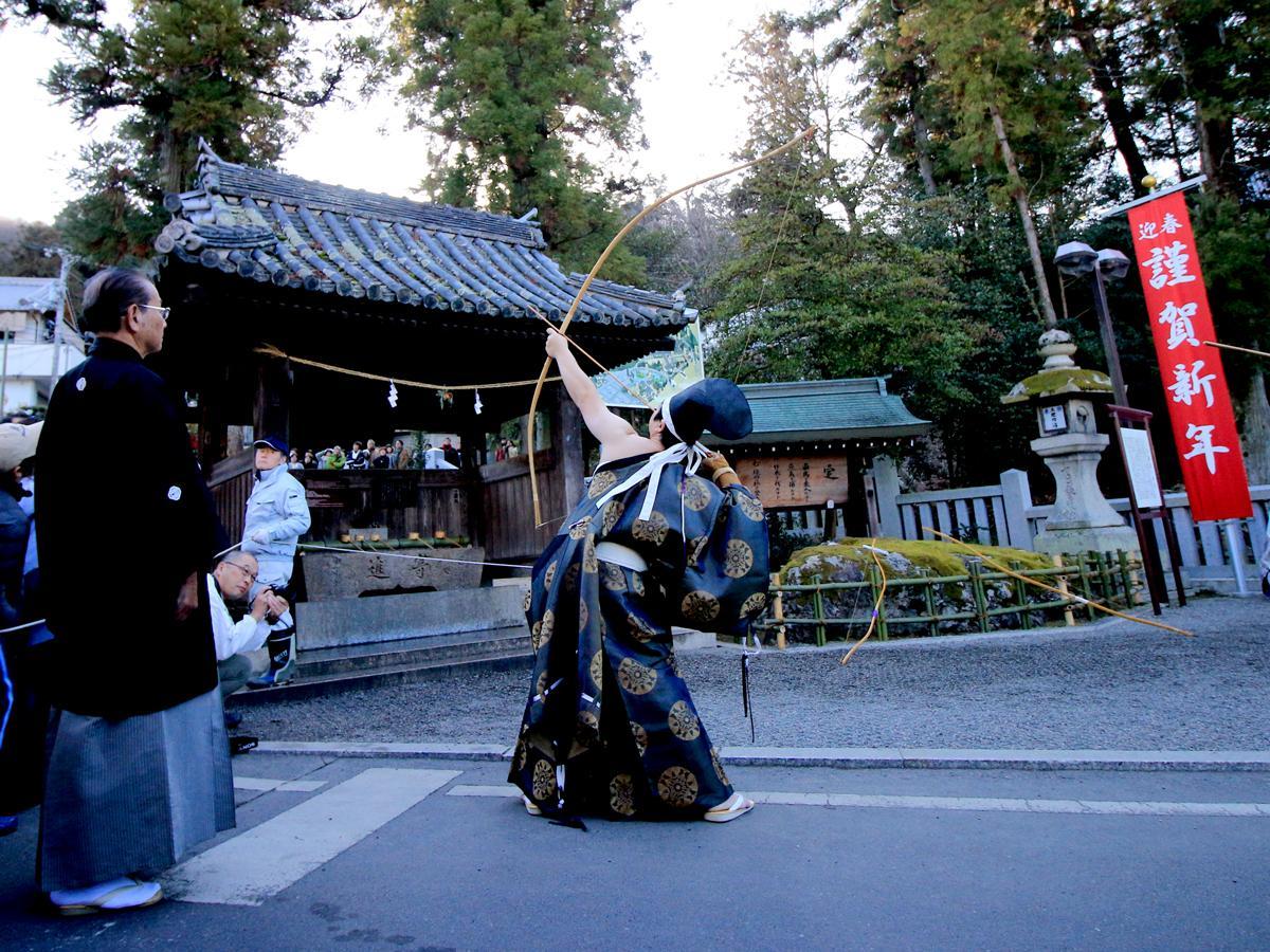 吉備津神社・矢置岩の前で矢を放つ神事の様子