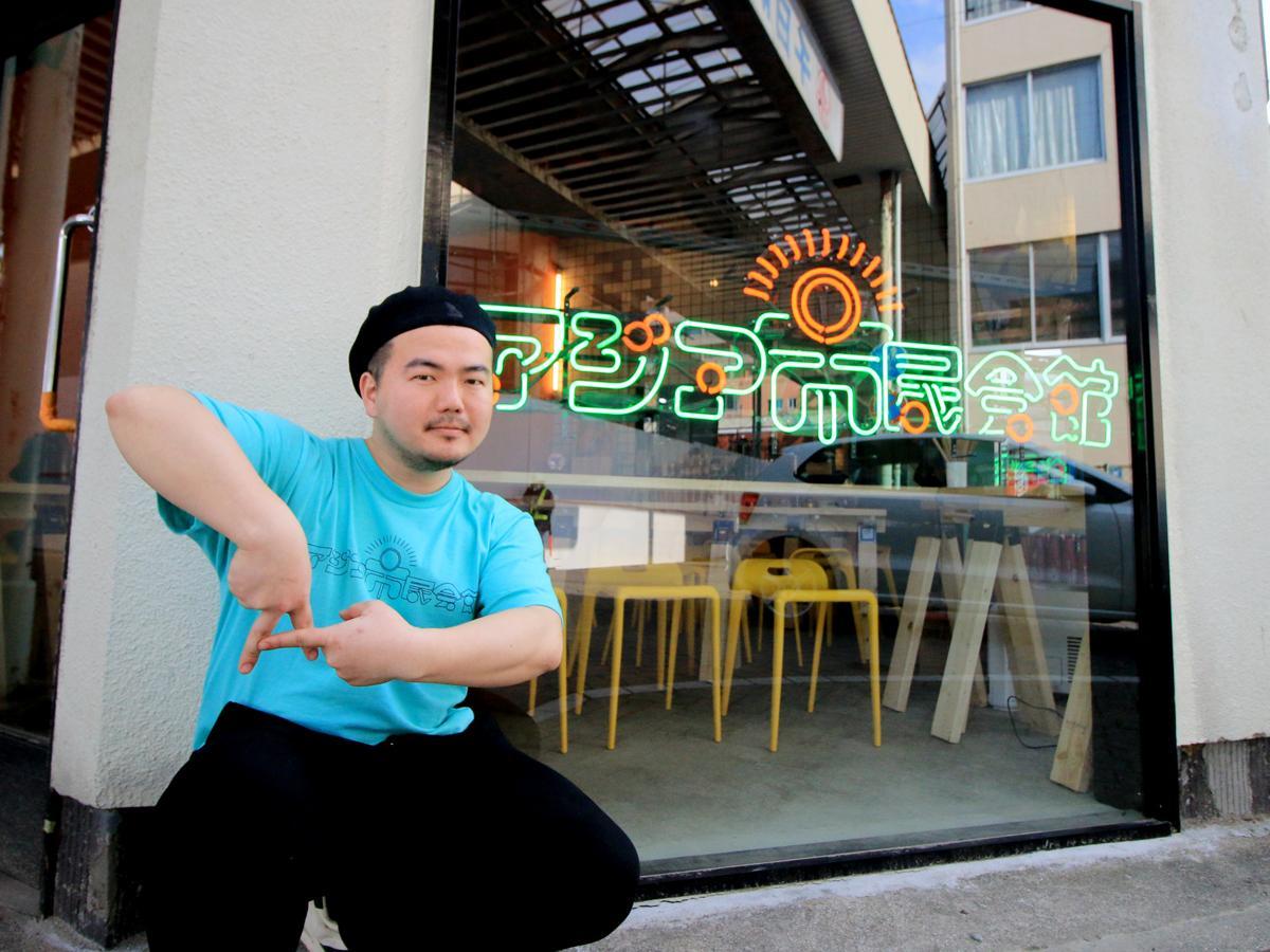 「アジア市民会館」のネオンサインの前でAポーズをする守屋直記さん