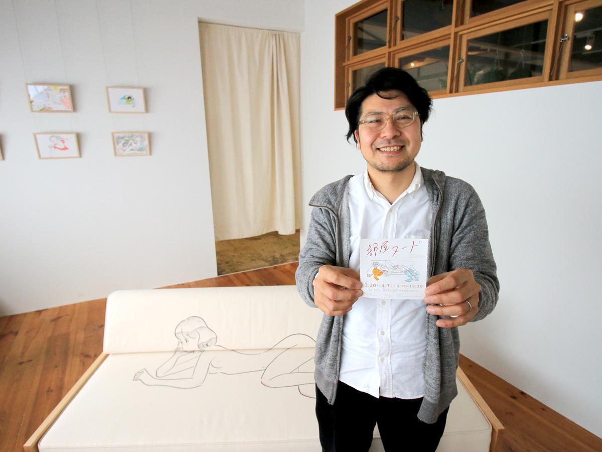 イールドのギャラリースペースで「部屋ヌード」店のチラシを持つ平井利幸さん