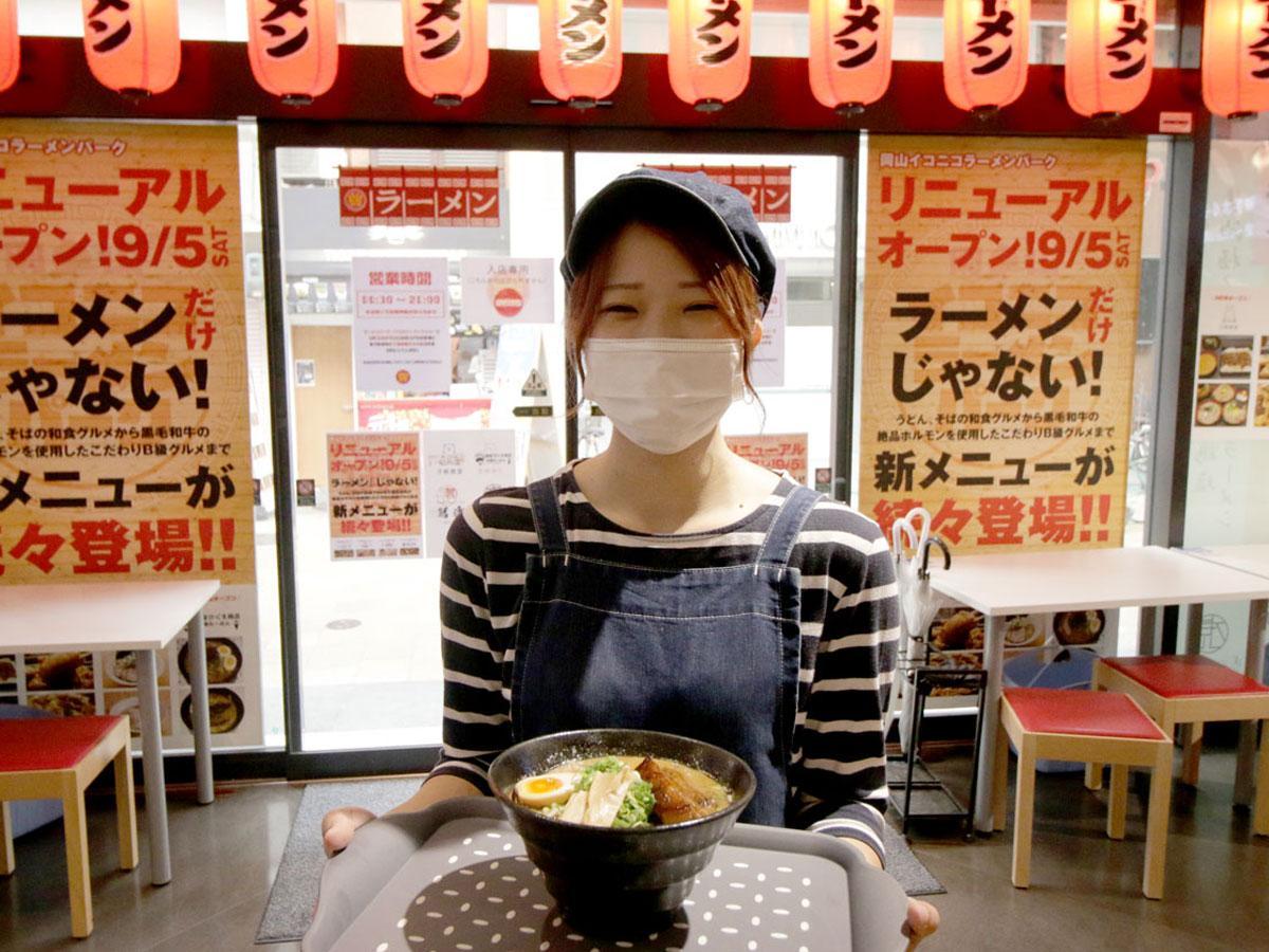 麺家ひぐま商店の「みそ煮込太肉ラーメン」を持つスタッフ