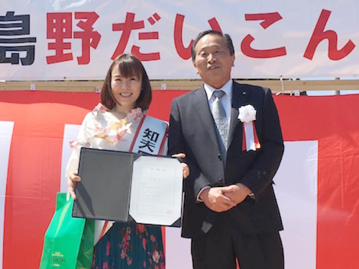 半崎美子さん(左)と平木伴佳知夫村長(右)