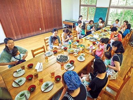 昼食のテーブルを囲む参加者らの様子