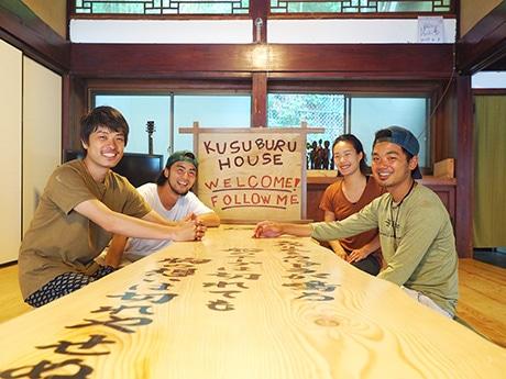 ゲストハウス「KUSUBURU HOUSE」を運営する岩井明人さん(写真奥左)と柴田悠平さん(同手前右)、佐々木鈴夏さん(同奥右)、嶋田和史さん(同手前左)。同ゲストハウスの居間で撮影