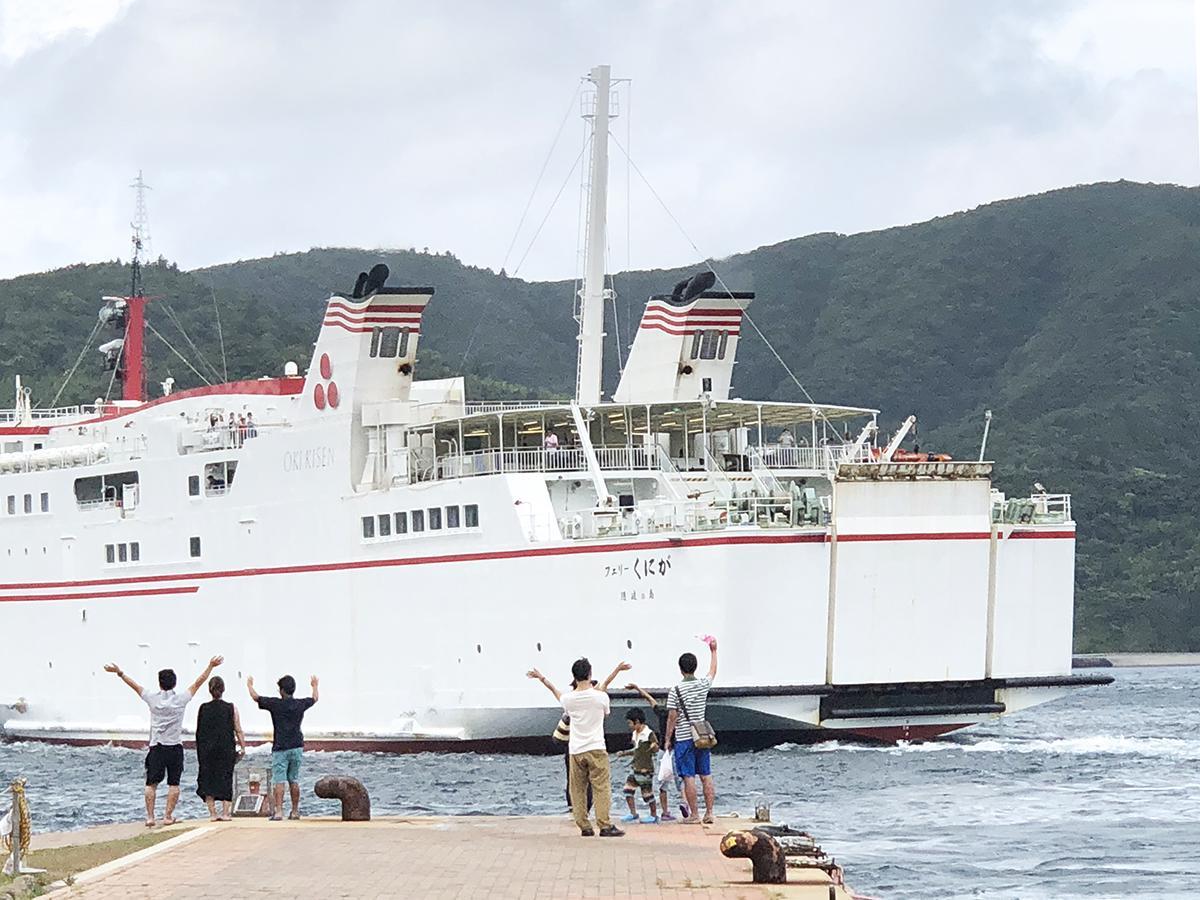 菱浦港で船を見送る人々の様子