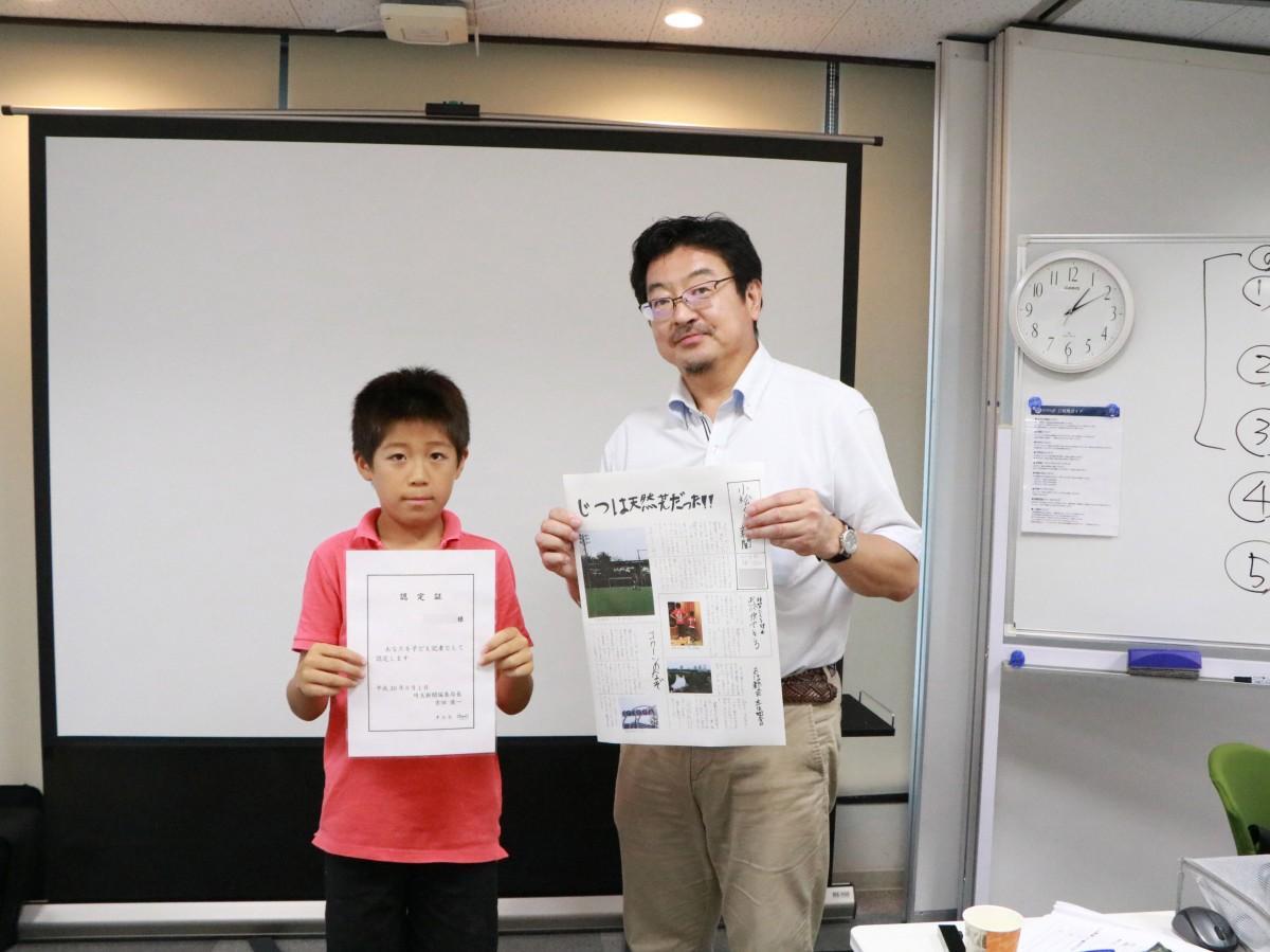 完成した新聞と子ども記者認定証を手にする参加者