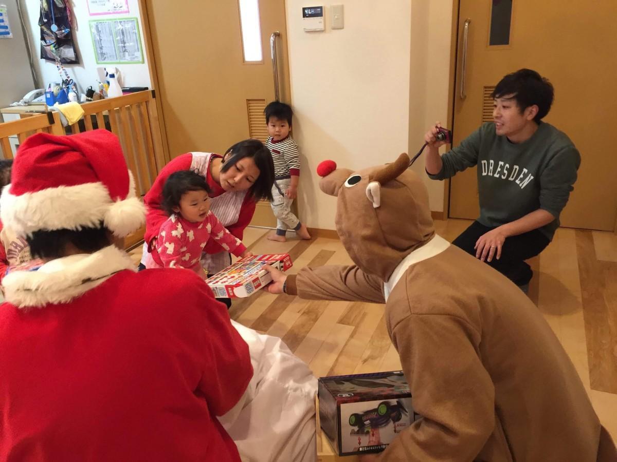 プレゼントを届けるサンタとトナカイに笑顔を見せる子ども