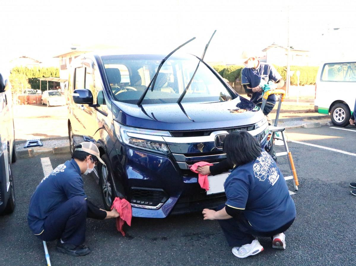 手洗いで隅々まで丁寧に車を洗うスタッフたち