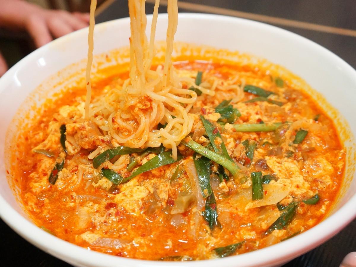赤いスープにニラや玉ねぎ、溶き卵が入った大宮担々麺