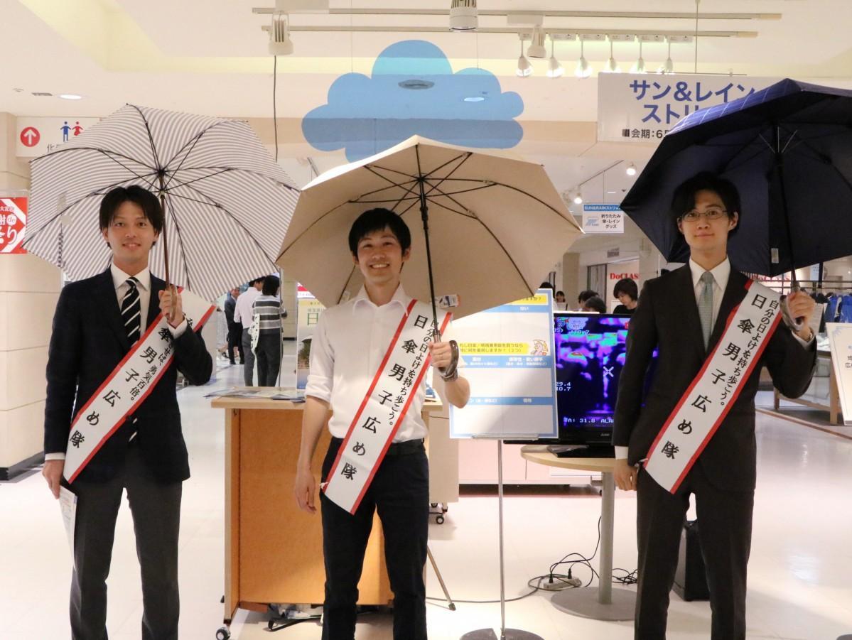 買い物客らに笑顔でPRする「日傘男子広め隊」