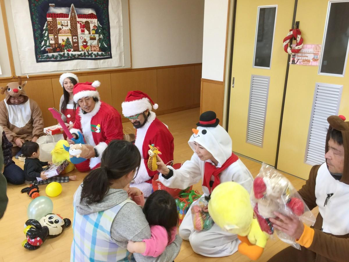 サンタやトナカイが子どもたちにプレゼントを手渡す