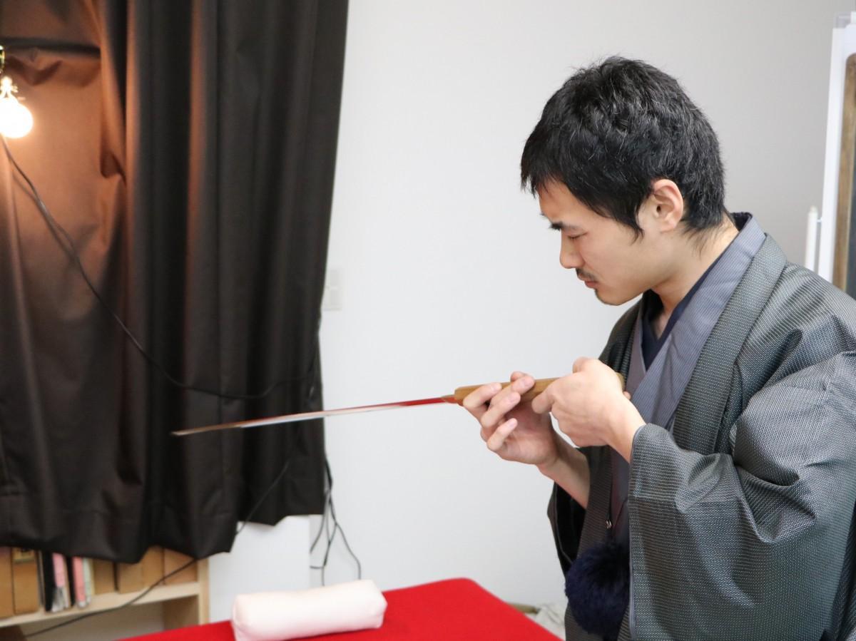 日本刀を見つめる店主の久津間さん